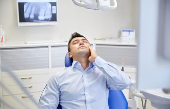 patient sitting in the dental chair holding his cheek