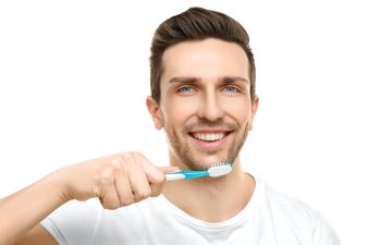 man brushing his teeth with a toothbrush