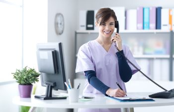 medical secretary smiling talking on the phone at the office
