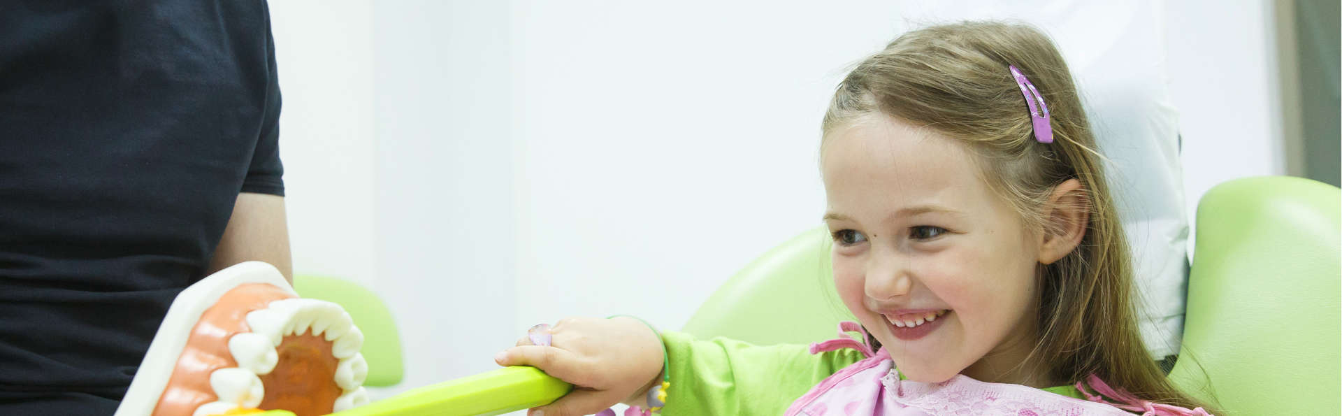 child look at the jaw while sitting on the dentist's chair